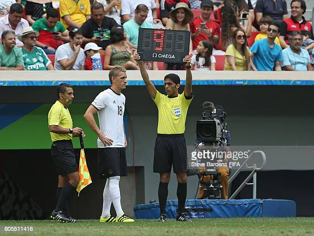 The 4th Official Fahad Al Mirdasi holds up the substitutes board during the Men's Quarter Final match between Portugal and Germany on Day 8 of the...