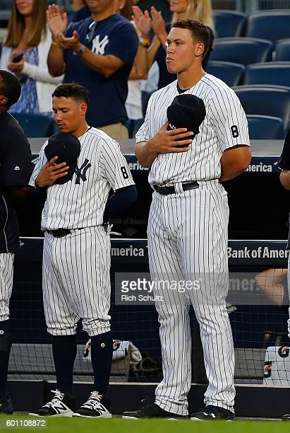 The 5' 10' Ronald Torreyes stands next to the 6' 7' Aaron Judge of the New York Yankees for the national anthem before a game against the Toronto...