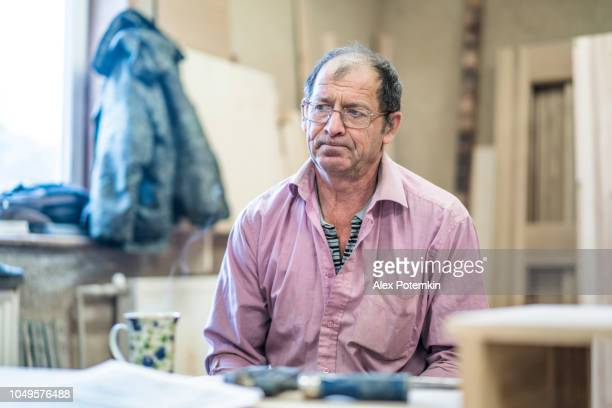 the 60-years-old senior, sashman, taking a break and resting with the cup of tea at the small wood manufacture - 55 59 years stock pictures, royalty-free photos & images