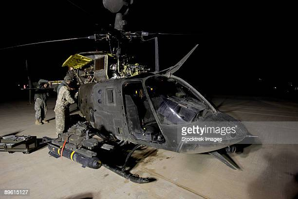The 6th Squadron, 17th Cavalry Regiment maintenance crew works on servicing the OH-58D Kiowa helicopter before its next mission.