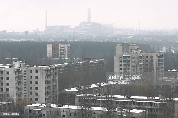 The abandoned tower blocks and trees of the town of Pripyat in the snow with Reactor No4 on the horizon 17th March 2006