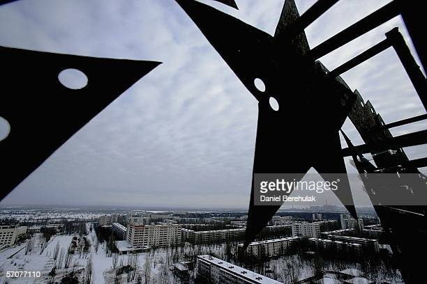 The abandoned town of pripyat and the Chernobyl Power Plant are seen through some scaffolding holding a remnant of the Soviet Union, the hammer and...