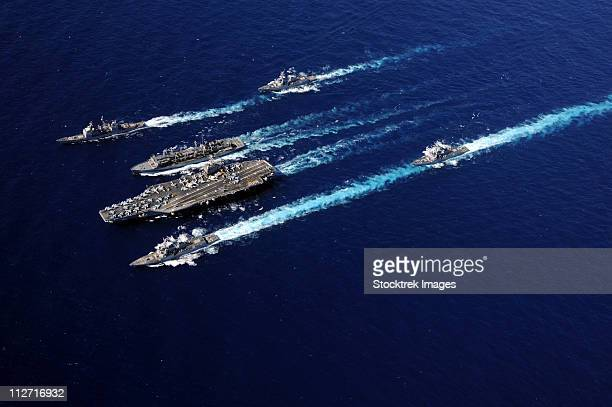 the abraham lincoln carrier strike group ships cruise in formation in the pacific ocean. - military ship stock pictures, royalty-free photos & images