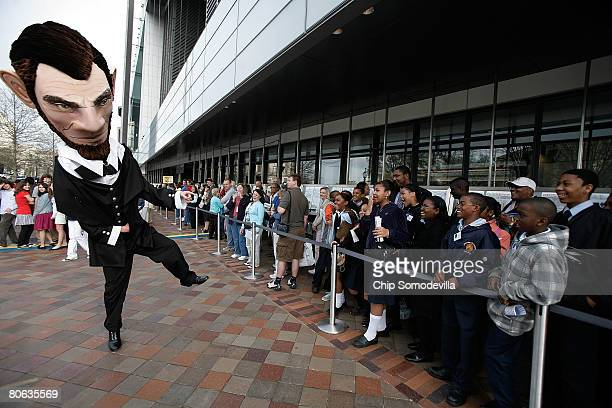 The Abraham Lincoln mascot from the Nationals Major League Baseball team entertains school children as they wait in line to enter the grand opening...