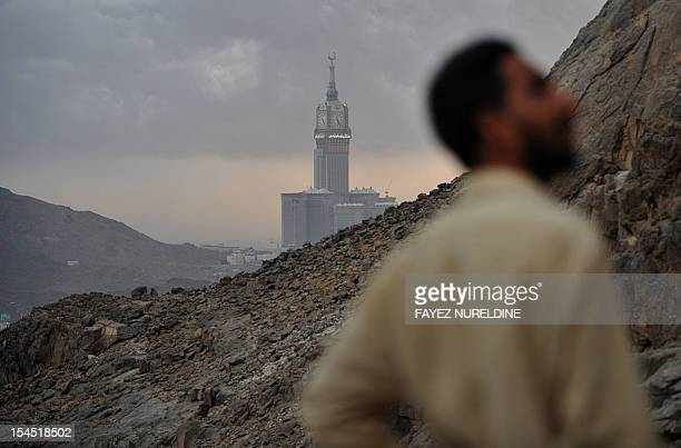 The Abraj AlBait Tower also known as the Mecca Royal Hotel Clock Toweris seen in the background as a Muslim pilgrim as they visit Jabal alNoor or...
