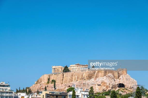 the acropolis of athens over modern buildings on a day with clear sky - column stock pictures, royalty-free photos & images