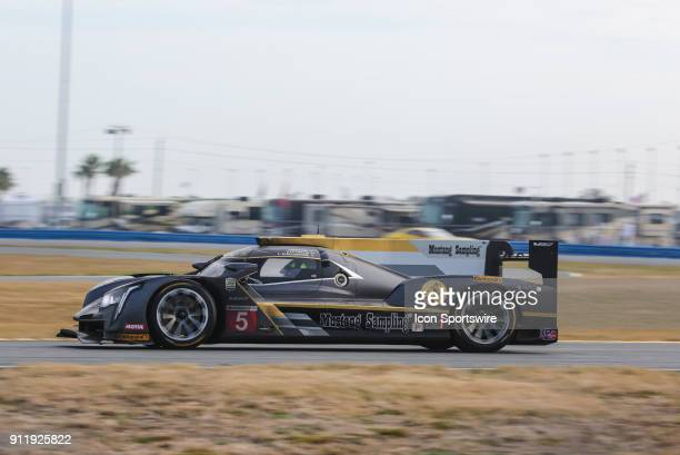 The Action Express Racing Cadillac DPiVR of Filipe Albuquerque Joao Barbosa and Christian Fittipaldi races through a turn during the Rolex 24 at...