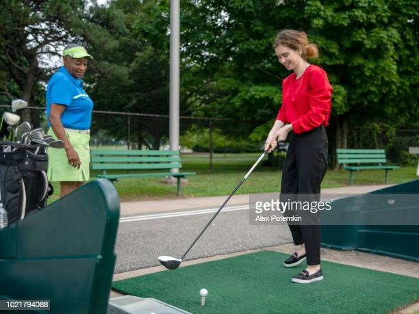 The active 77-years-old senior African-American woman teaching the 18-years-old Caucasian girl to play golf.