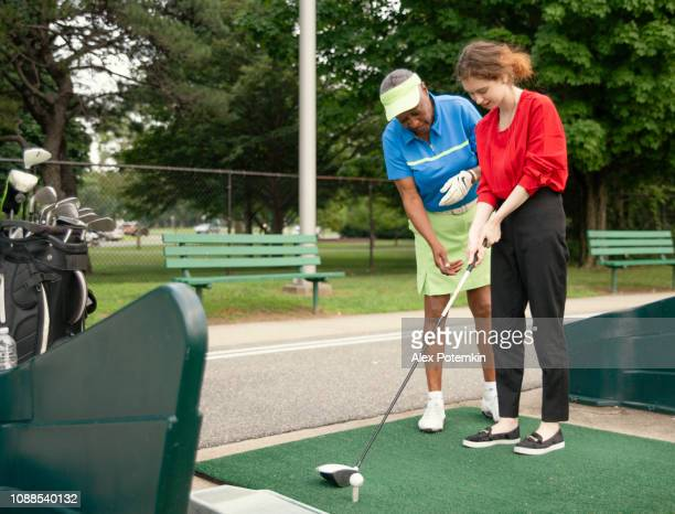 L'active âgé de 77 ans senior femme afro-américaine enseigner la fille de race blanche âgé de 18 ans pour jouer au golf.