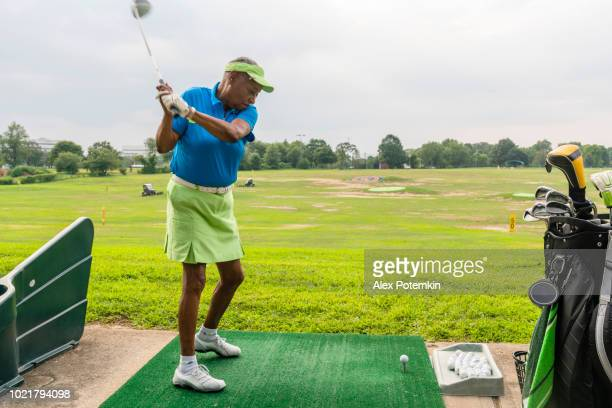 The active, optimistic 77-years-old senior Black woman playing golf