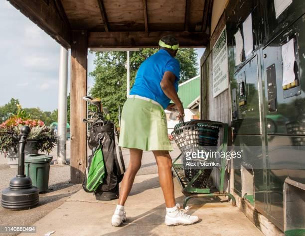 L'actif, optimiste 77-ans âgé aîné femme noire jouant au golf-achetant des balles