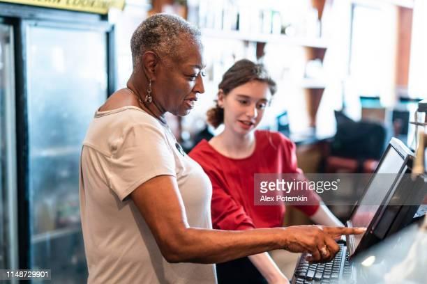 L'aîné actif, 77-ans, femme d'affaires afro-américaine, propriétaire d'entreprise, l'enseignement du nouvel employé, la jeune fille blanche caucasienne de 18 ans, comment utiliser la caisse enregistreuse informatisée dans le petit restaurant