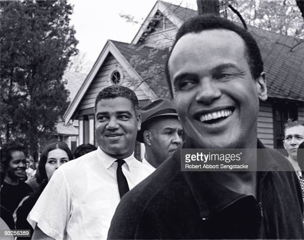 The actor and civil rights ativist Harry Belafonte smiles broadly while marching with National Urban League director Whitney Young and NAACP...