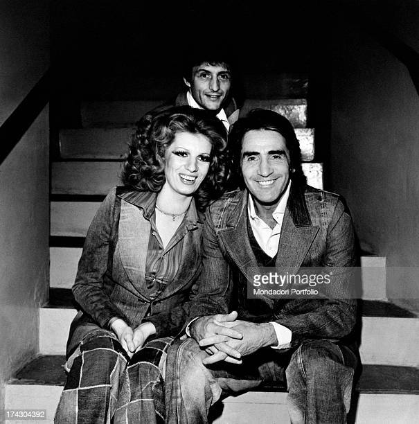 The actor and comedian Walter Chiari poses looking amused with the singers Iva Zanicchi and Tony Renis All three are sitting on a staircase during a...