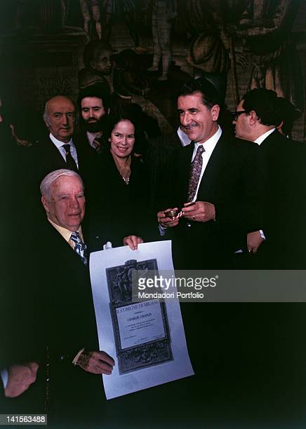 The actor and film director Charlie Chaplin accompanied by his wife Oona O'Neil receives the Freedom of the City parchment from Milan mayor Aldo...
