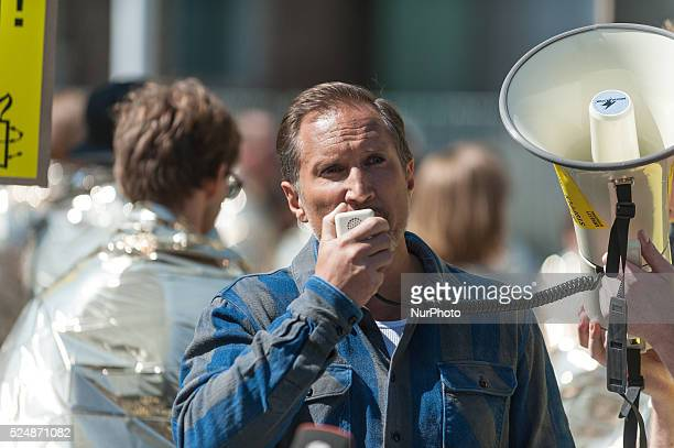 The actor Benno F��hrmann holds during a campaign by Amnesty International against the current refugee policy on in Berlin Germany in front of the...