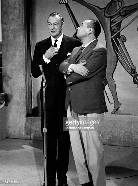The actor from Rome Mario Riva, with crossed arms, is listening to the US actor Gary Cooper, the guest star of this episode of the musical quiz Il...