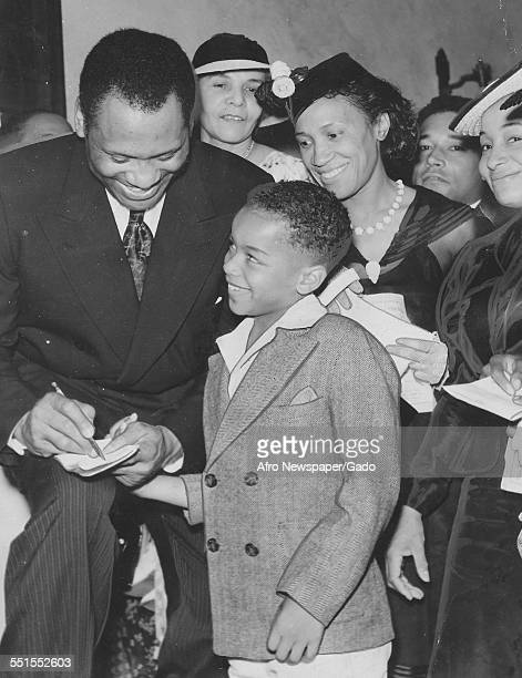 The actor, singer and movie star Paul Robeson signing the autograph book of a young boy at a concert, 1930.