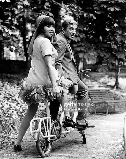 The actor Ugo Tognazzi and the dancer and singer Maria Grazia Buccella sitting on a tandem on the set of the movie Dismissed on His Wedding Night...