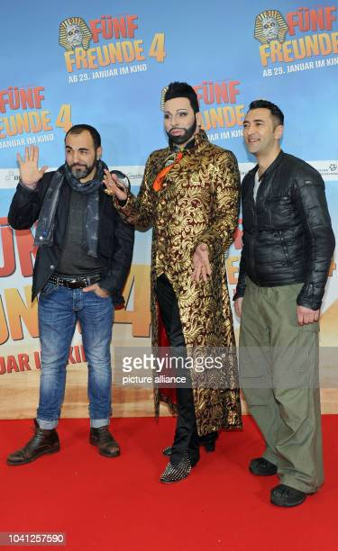 The actors Adnan Maral and Mehmet Kurtulus and designer Harald Gloeoeckler pose in front of the movie poster at the premiere of their movie 'Fuenf...
