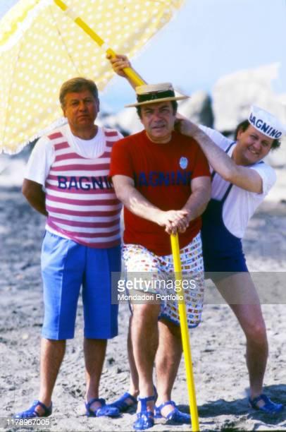 The actors Paolo Villaggio Lino Banfi and Massimo Boldi at the beach on the set of the film Scuola di ladri Italy 1986