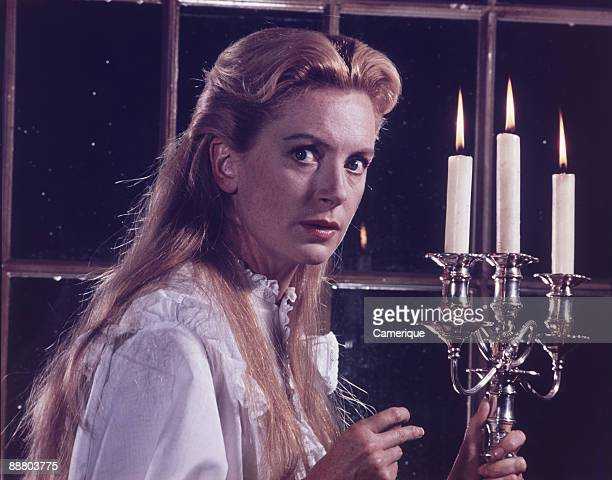 The actress Deborah Kerr shows a mild look of fear in a scene from an unidentified move ca1960s She is wearing a nightgown and carrying a candelabra...