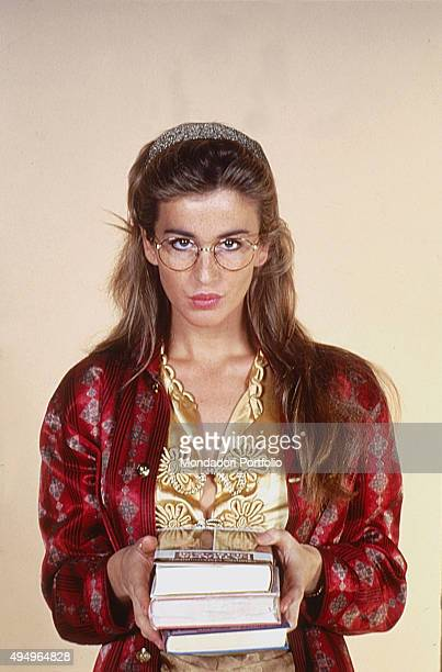 The actress Eva Robin's with eyeglasses and a pile of books in the TV show 'Lupo solitario' broadcasted by Italia uno Photo shooting Italy 1987