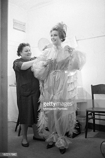 The actress Ilaria Occhini is being dressed up in a dressing room Teatro Lirico Milan November 23 1960