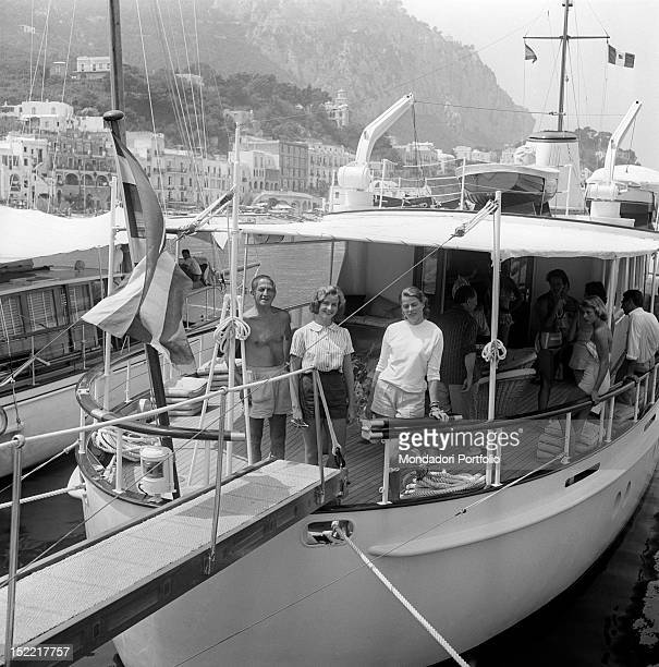 The actress Ingrid Bergman and her daughter Pia Lindstrom with some friends inside a yacht berth on the pier. Capri, the '50s.