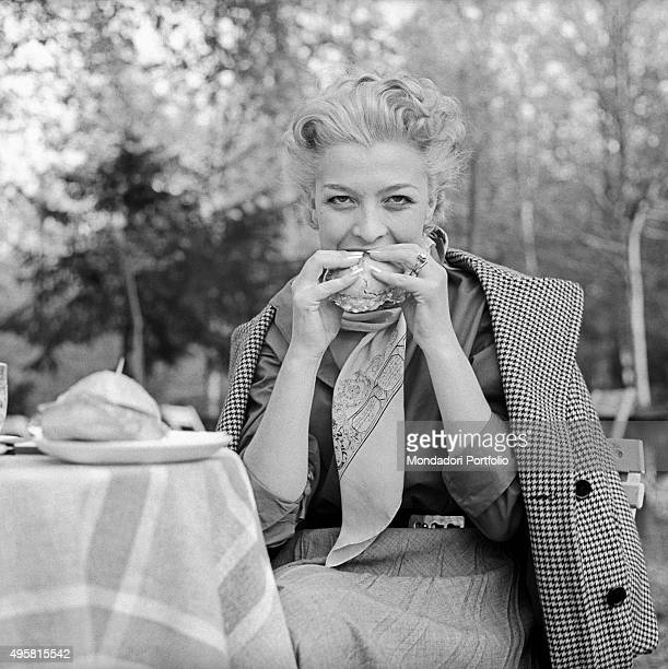 The actress Isa Barzizza bites a salami sandwich with taste sitting at a small table in a park with her overcoat placed on her shoulders Italy May...