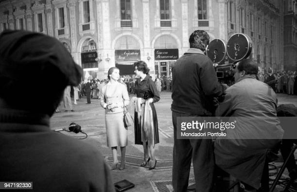 The actress Jacqueline Sassard converses with an assistant on the set of the movie Nata di marzo while members of the film crew are filming them with...