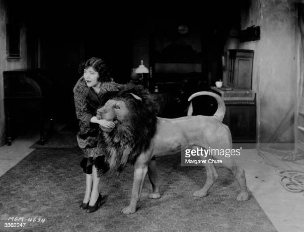 The actress Renee Adoree plays with a stuffed lion during a break in the filming of 'The Show' in which she stars with John Gilbert