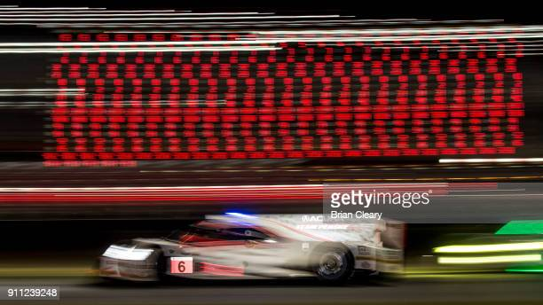 The Acura DPi of Dane Cameron Juan Pablo Montoya of Colombia and Simon Pagenaud of France races past a scoring tower at night during the Rolex 24 at...