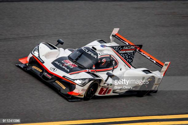 The Acura DPi of Ricky Taylor Helio Castroneves of Brazil and Graham Rahal races on the track during the Rolex 24 at Daytona at Daytona International...
