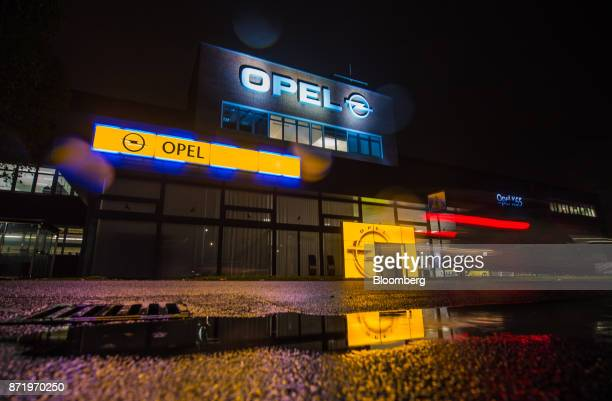 The Adam Opel AG logo sits illuminated outside an entrance at the Opel automobile factory in Ruesselsheim Germany on Thursday Nov 9 2017 PSA...