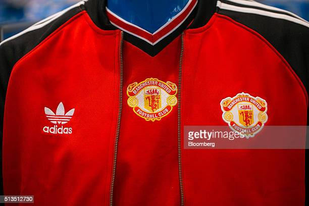 The Adidas logo sits on a Manchester United Football Club tracksuit top inside the Adidas AG store at the company's headquarters in Herzogenaurach...
