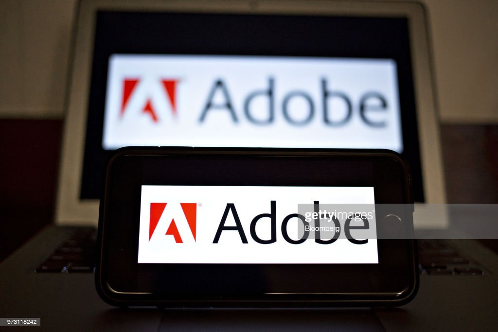 The Adobe Systems Inc. logo is displayed on an Apple Inc. iPhone and laptop computer in an arranged photograph taken in Tiskilwa, Illinois, U.S., on Friday, June 8, 2018. Adobe Systems Inc. is scheduled to release earnings figures on June 14. Photographer: Daniel Acker/Bloomberg via Getty Images