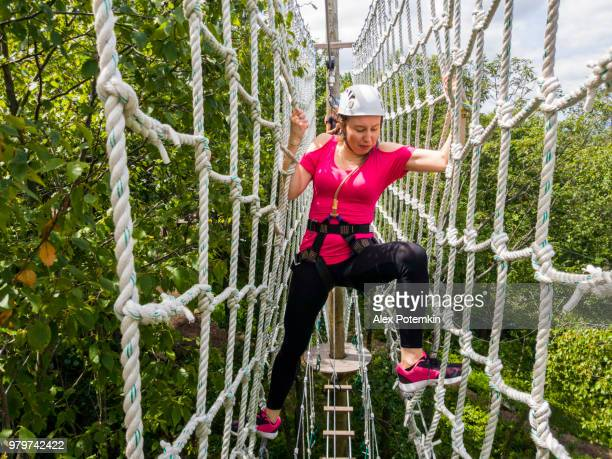 the adult woman passing the zip line. mobile photo. - alex potemkin or krakozawr stock pictures, royalty-free photos & images