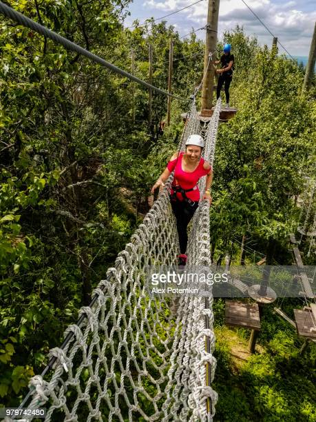 the adult woman passing the zip line. mobile photo. - pocono mountains stock pictures, royalty-free photos & images
