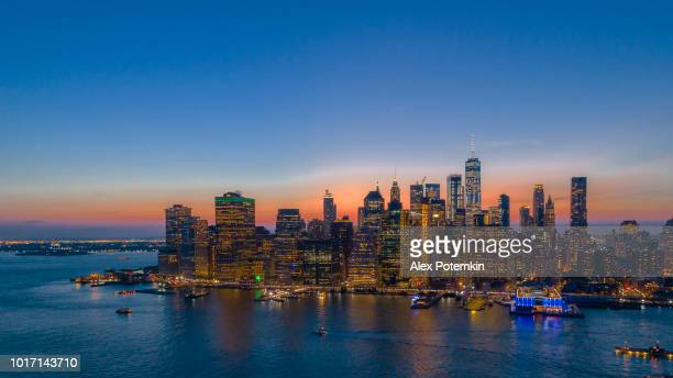 The aerial scenic panoramic view to Manhattan Downtown from Brooklyn Heights over the East River at the sunset.