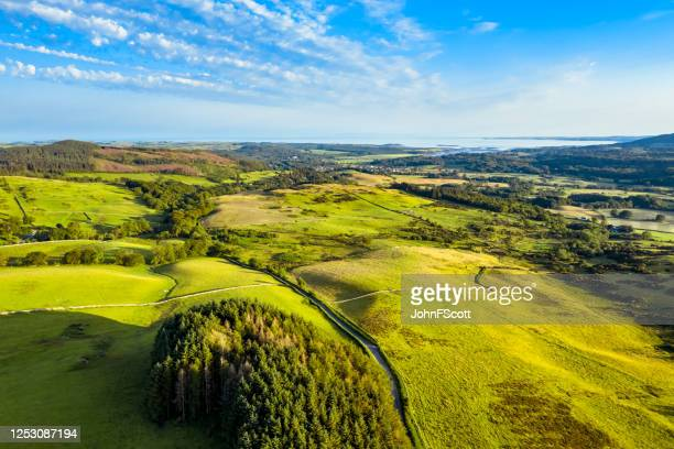 the aerial view across rural scotland towrds the sea in the early evening of a summer day. - johnfscott stock pictures, royalty-free photos & images