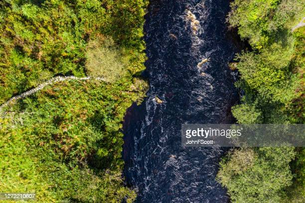 the aerial view from a drone of a river flowing in remote rural dumfries and galloway - johnfscott stock pictures, royalty-free photos & images
