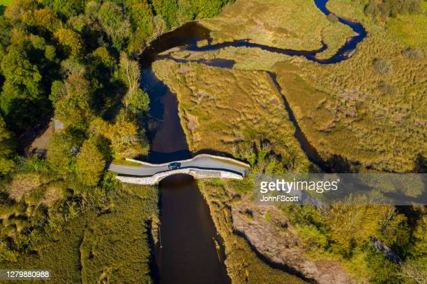 the aerial view from a drone of an old stone bridge in dumfries and galloway south west scotland - johnfscott stock pictures, royalty-free photos & images