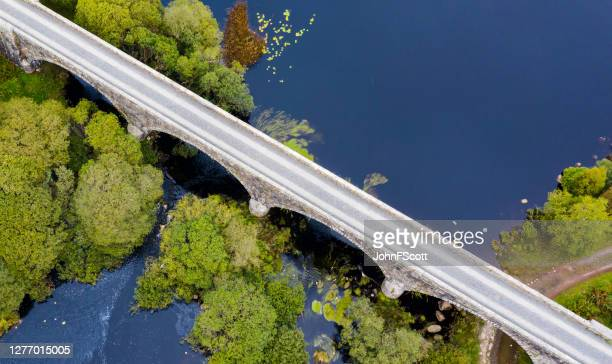 the aerial view looking down on a disused railway viaduct in rural scotland - johnfscott stock pictures, royalty-free photos & images