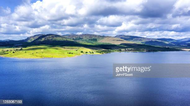 the aerial view of a scottish loch captured from a drone on a bright summer day - johnfscott stock pictures, royalty-free photos & images