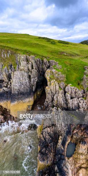 the aerial view of the entrance to a cave in cliffs on the coastline of dumfries and galloway, south west scotland. - johnfscott stock pictures, royalty-free photos & images