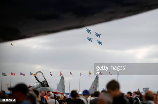 The aerobatics team Russian Falcons in Su-27 fighter jets flies over a Tu-144 on display at the MAKS 2009 international aerospace show outside Moscow...