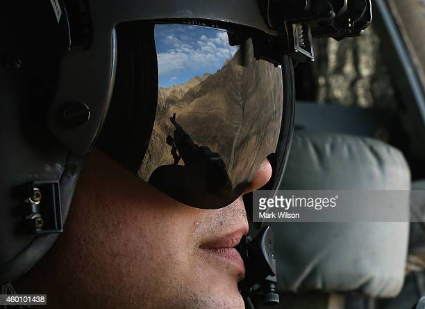 The Afghan mountains are reflected in the visor of a US Army Airborne CH47 Chinook window gunner while flying behind Defense Chuck Hagel who was...