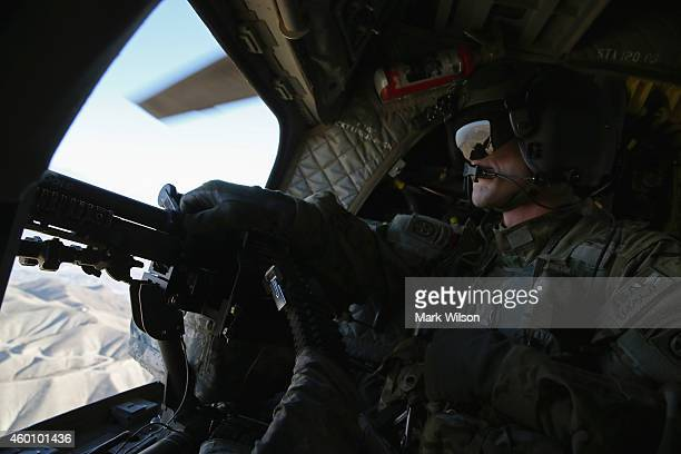 The Afghan mountains are visable as a US Army Airborne CH47 Chinook window gunner looks out while flying behind Defense Chuck Hagel's helo who was...