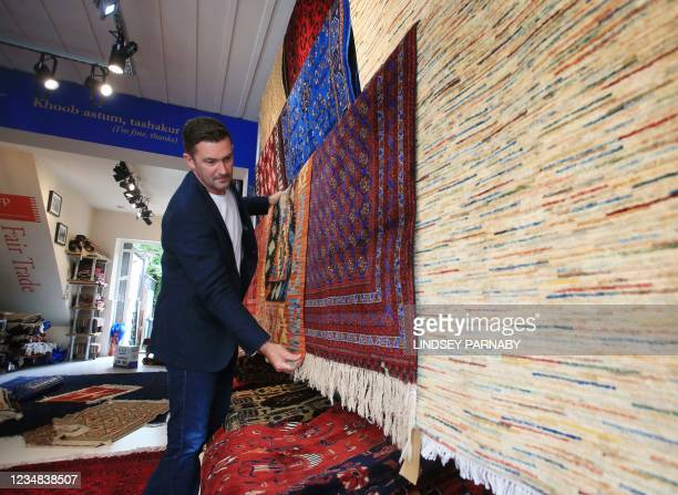 The Afghan Rug Shop owner James Wilthew arranges a display at his shop in Hebden Bridge, northern England, on August 20, 2021. - Overseas businesses...